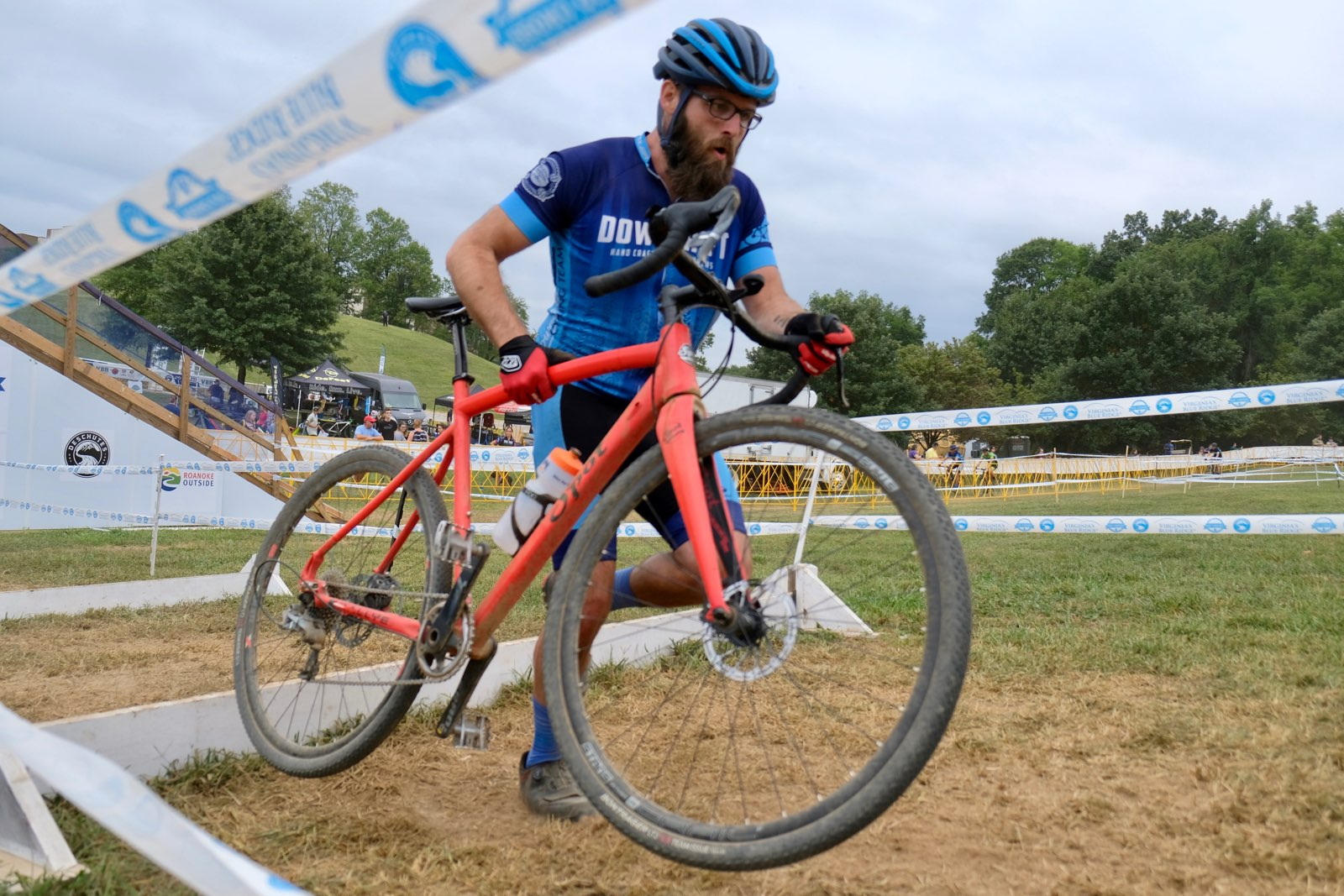 competitive cyclist carrying his bike on cyclocross course