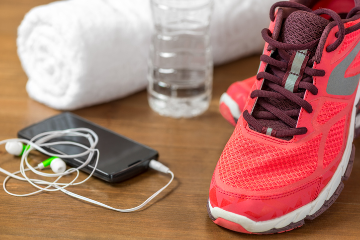 Sneakers, a water bottle, a towel and a phone with headphones.