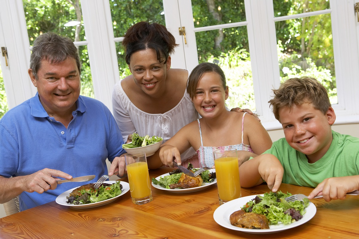 family of four eating a healthy meal and smiling