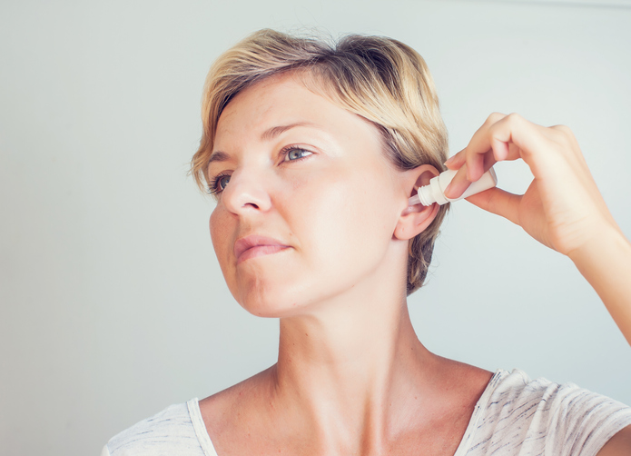 woman with blonde hair applying over-the-counter ear drops to remove ear wax