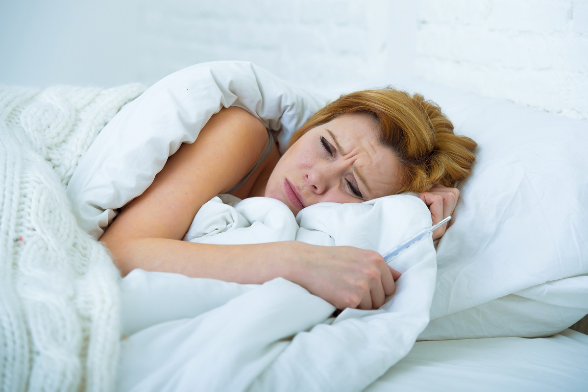 woman looking pained while trying to rest on white sheets and pillow