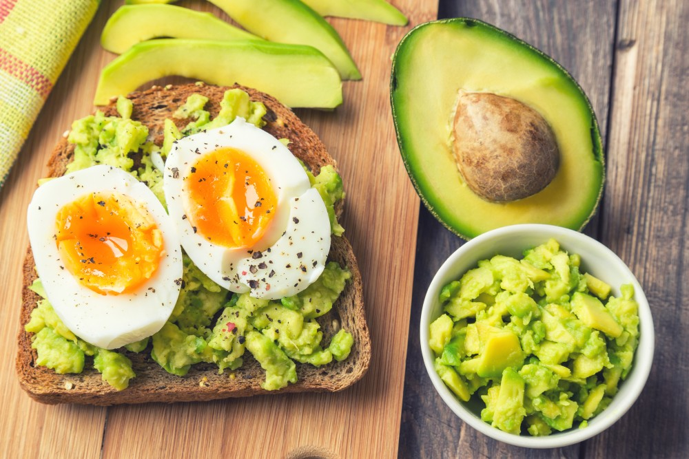 Overview of a slice of toast topped with avocado spread and soft boiled eggs, on a rustic wooden cutting board.