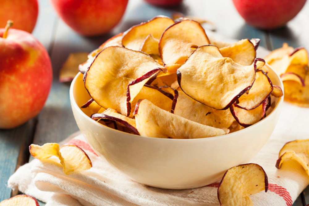 A bowl of homemade baked apple chips, with fresh fall apples in the background.