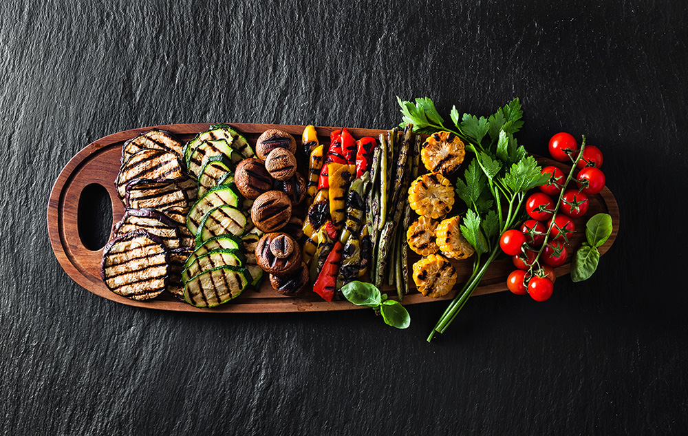 wooden tray artfully displayed with a variety of grilled vegetables