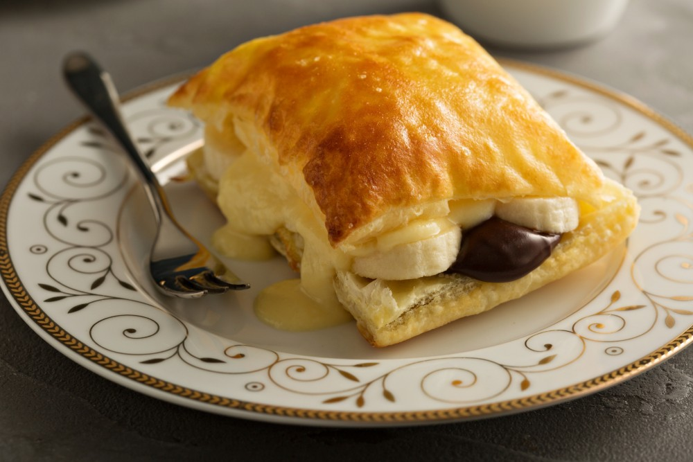 Slice of puff pastry filled with chocolate and banana, set with a fork on a vintage plate.