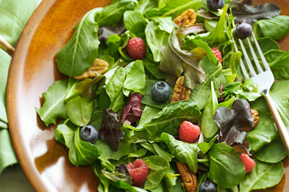 Close up of wooden bowl filled with greens, mixed nuts and fresh berries.