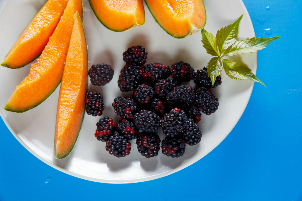 Cantaloupe slices, whole blackberries and sprigs of mint arranged on a white plate against a bright blue background.