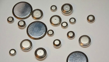 a dozen or so button batteries scattered on a white background