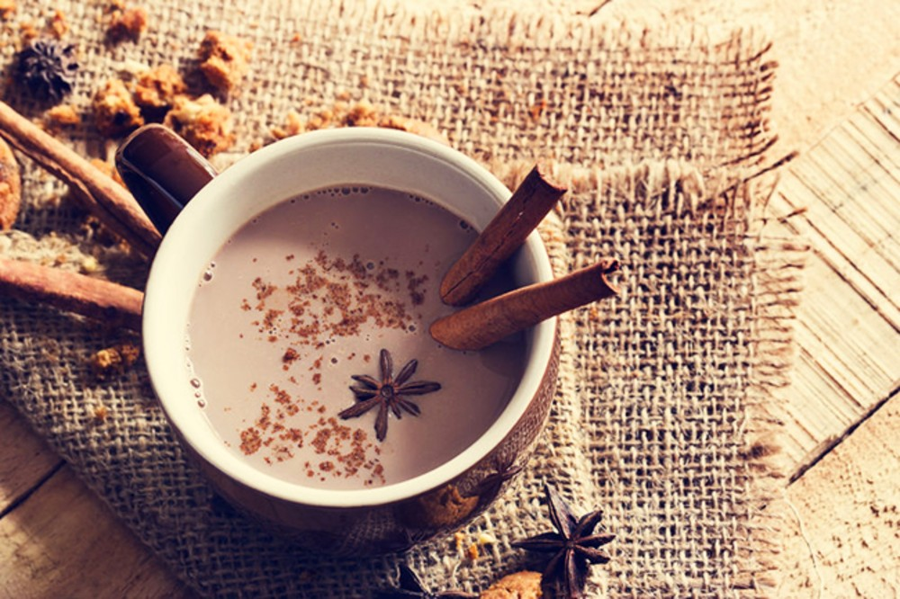A cup of chai hot chocolate with cinnamon sticks.