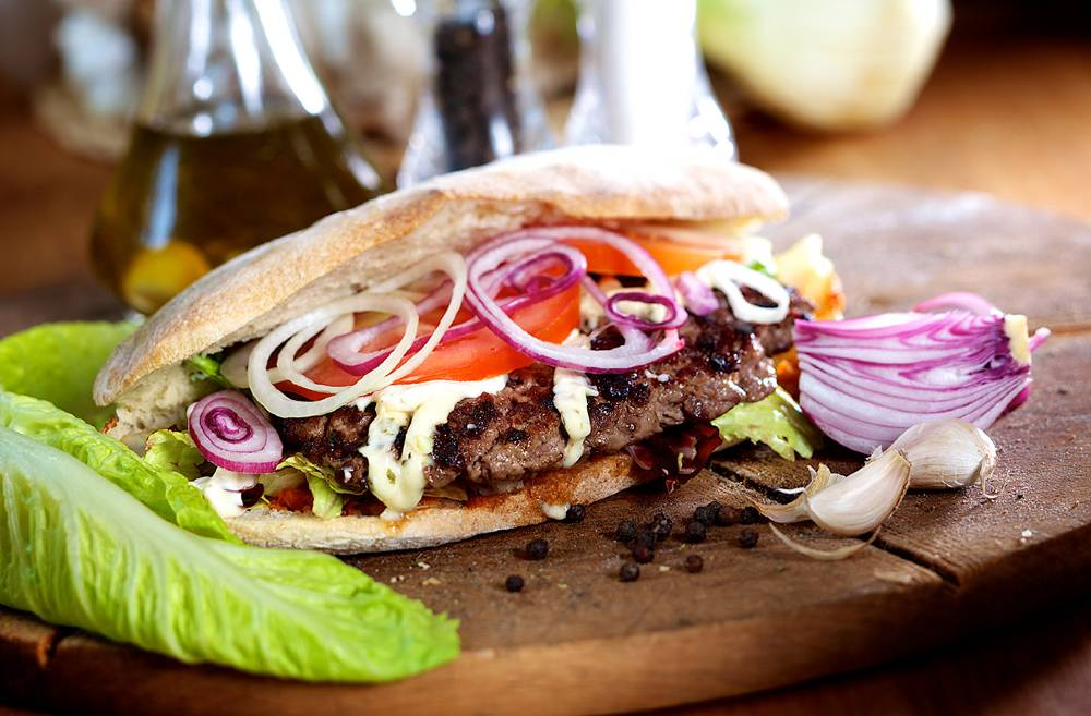 Burger with red onions served in a pita, with lettuce leaves and garlic cloves beside it, on a wooden table.