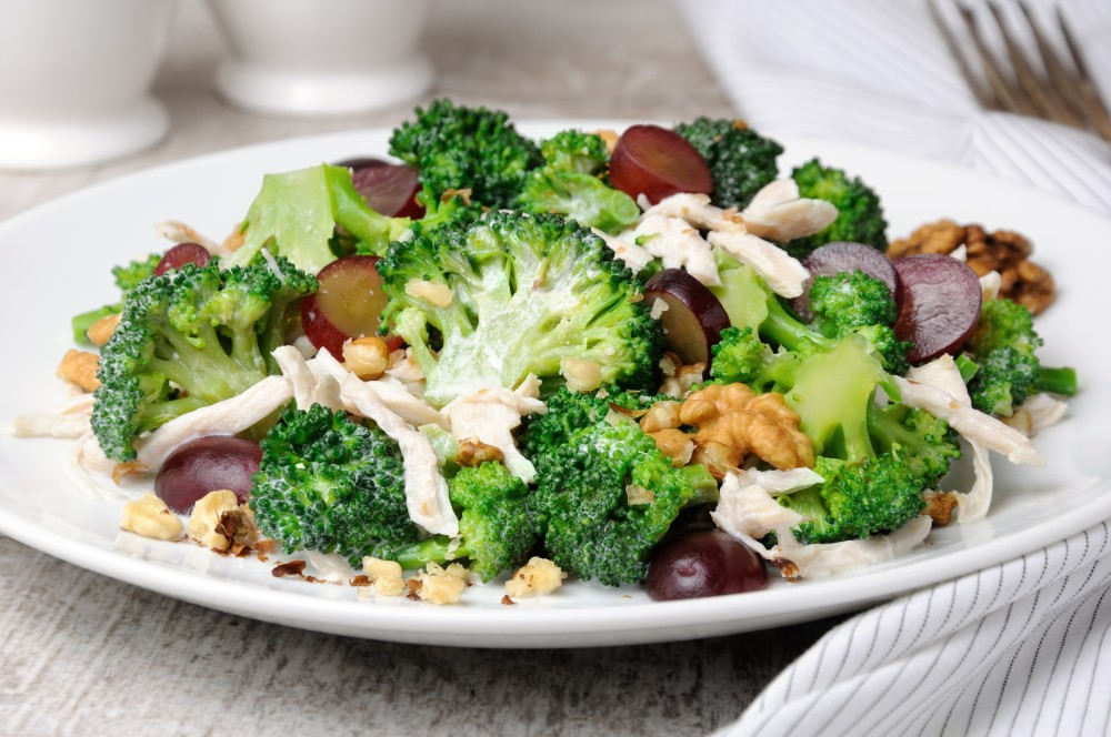 A plate of broccoli salad with grapes, walnuts and yogurt dressing.