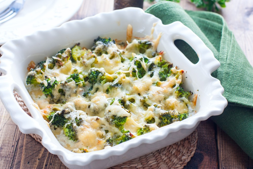 Porcelain casserole dish, filled with broccoli chicken pasta casserole, on a rustic table setting.