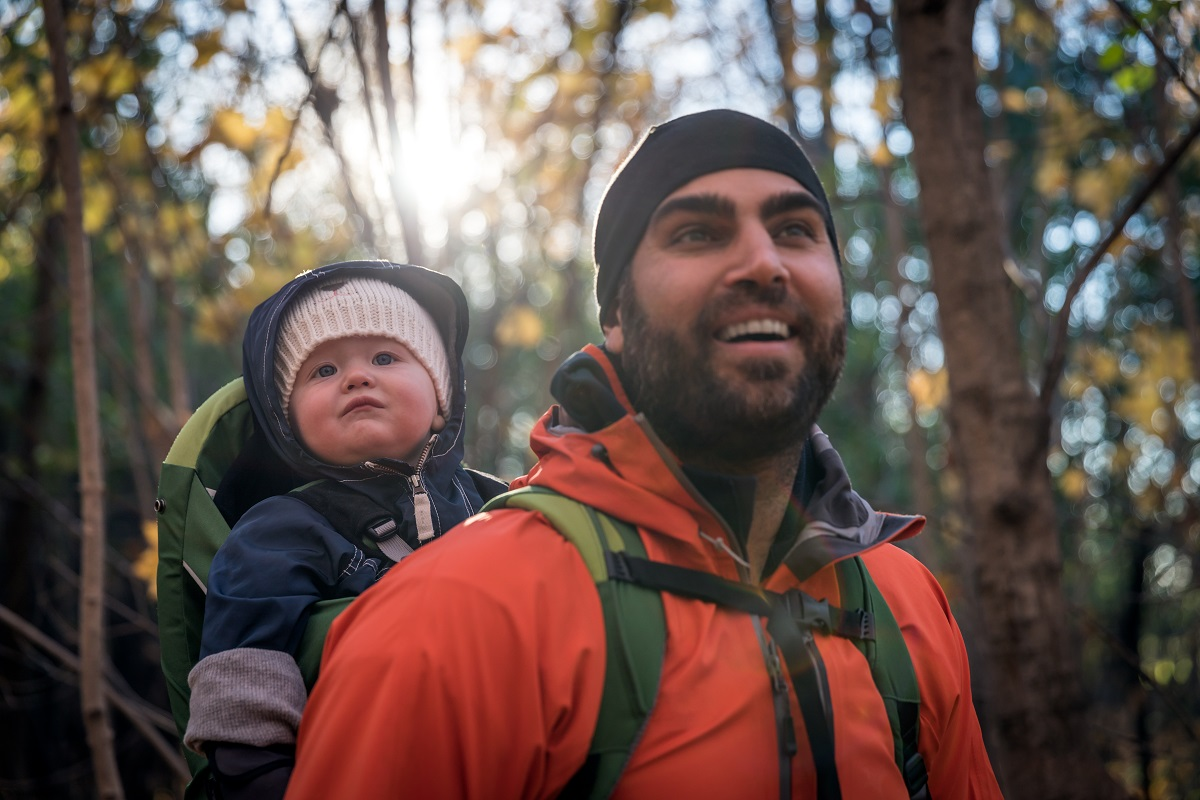 bust view of young father hiking in winter with baby in backpack