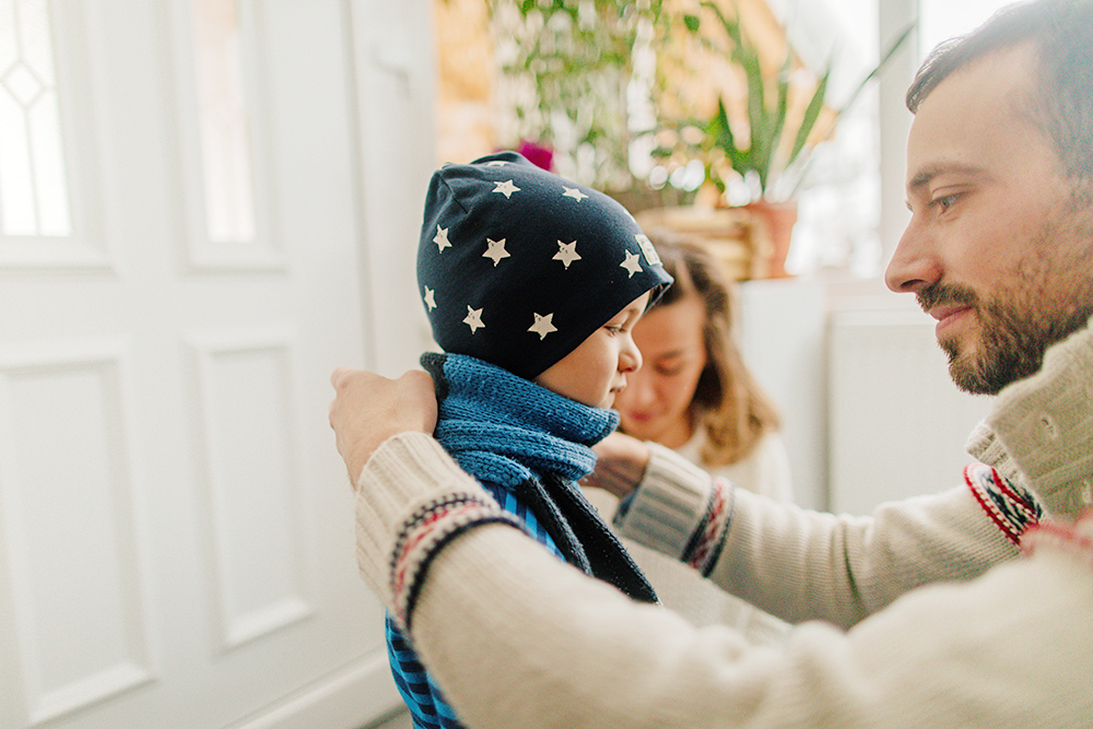 dad helping son put on winter hat, scarf and layers of clothes before going outside