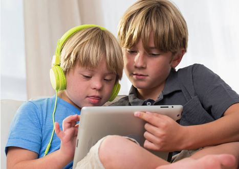 boy helping younger boy with down syndrome use tablet and headphones