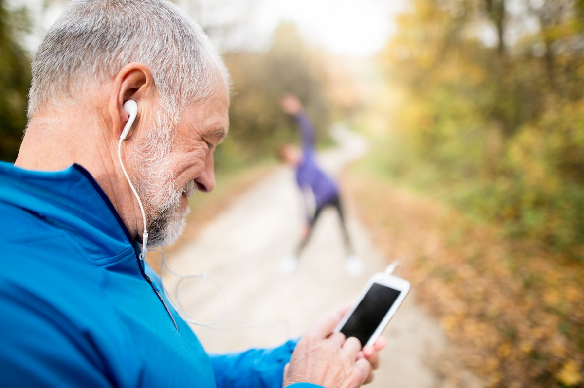 senior man using smartphone on trail with senior woman stretching in background