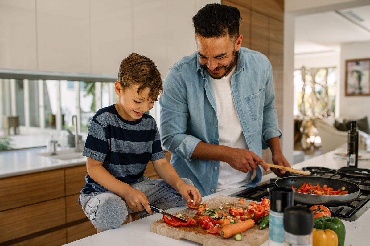 father and son preparing a meal together in modern kitchen