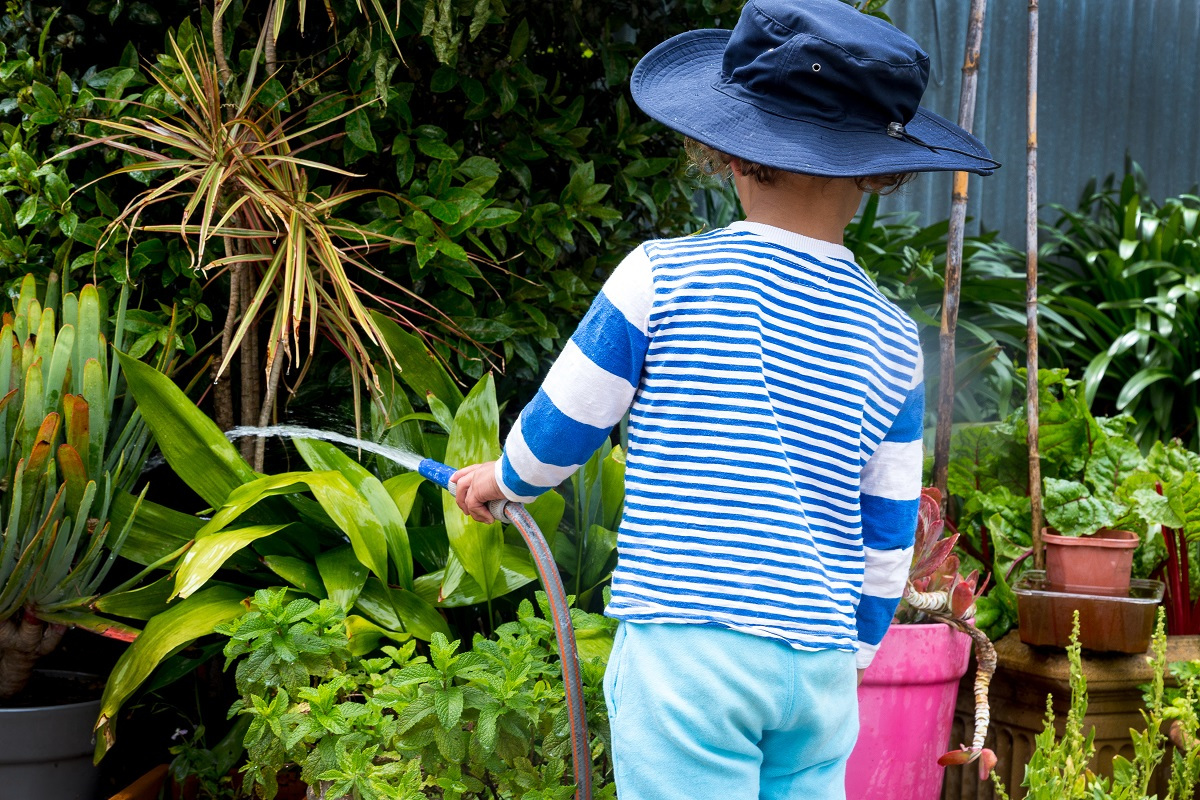 child in protective long sleeves and sun hat watering a garden