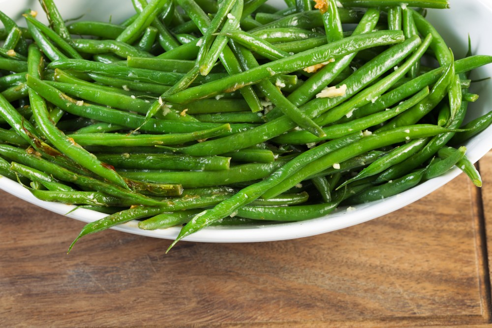 A plate of cooked green beans in herb dressing.