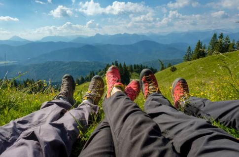 scenic view of mountains with three pairs of hikers' legs in closeup