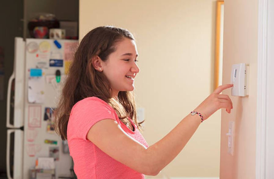 teen girl setting digital home alarm in kitchen with refrigerator in background