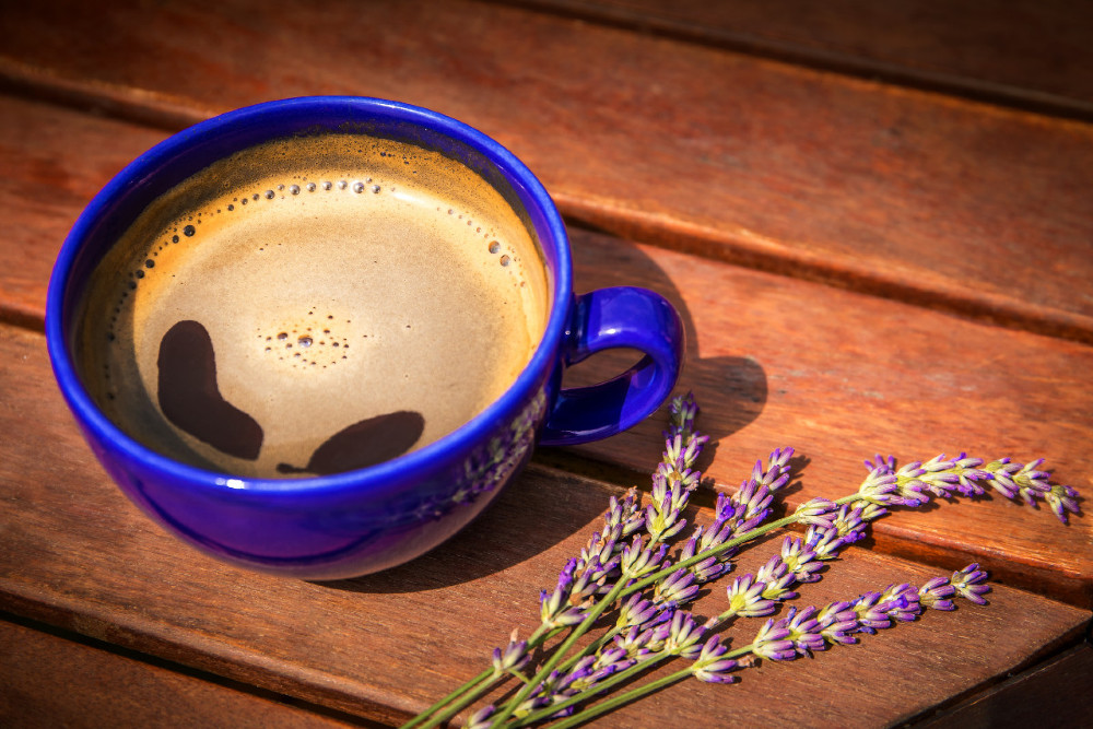 View of a mug of freshly-brewed lavender chai latte on a rustic wooden table.