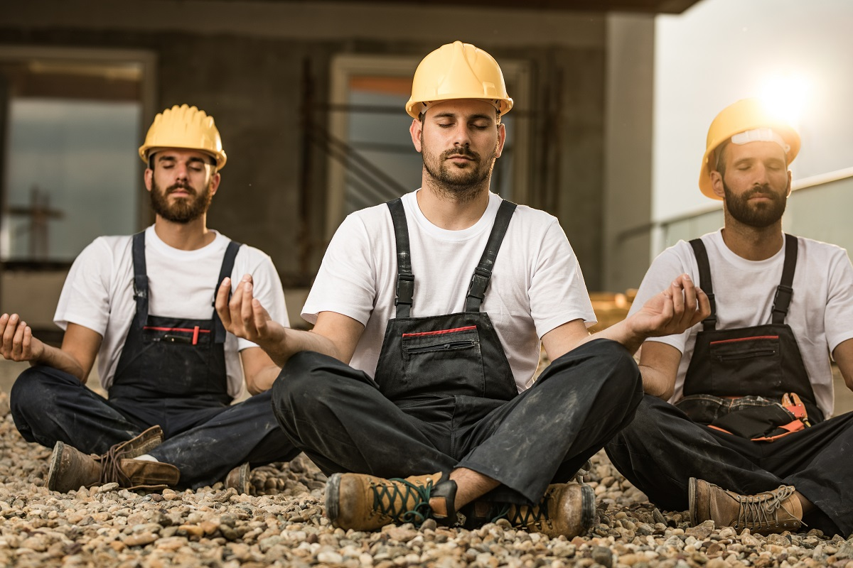 three men in construction gear and hardhats sitting crosslegged and calmly meditating