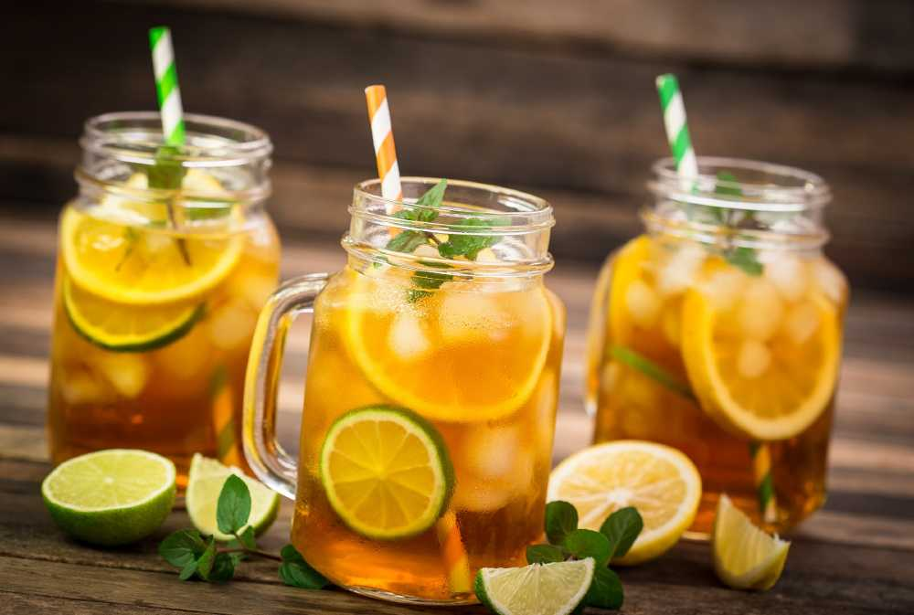 Mason jars filled with green tea and citrus slices, served with colorful straws, on a rustic wooden table