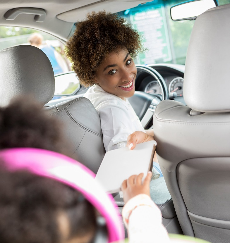 mom in driver's seat smiling and handing digital tablet to child in back seat