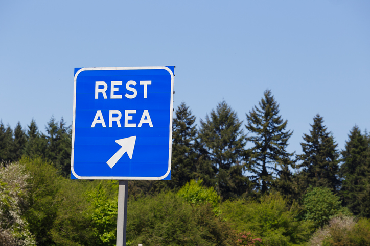 blue rest area sign on highway pointing right