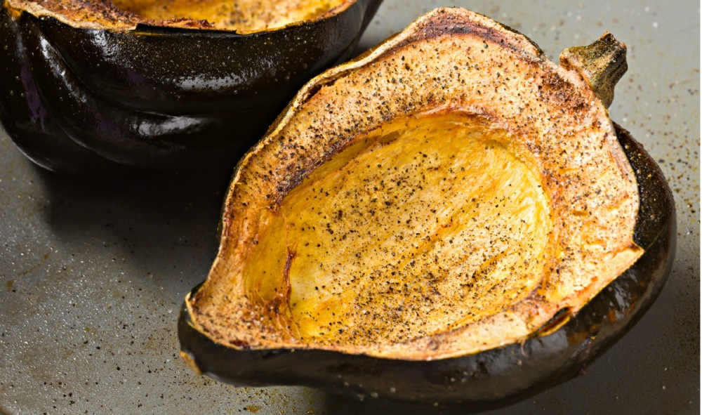 Two halves of a roasted acorn squash.