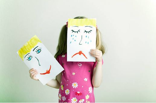 child holding drawings of happy and sad faces in front of her own face