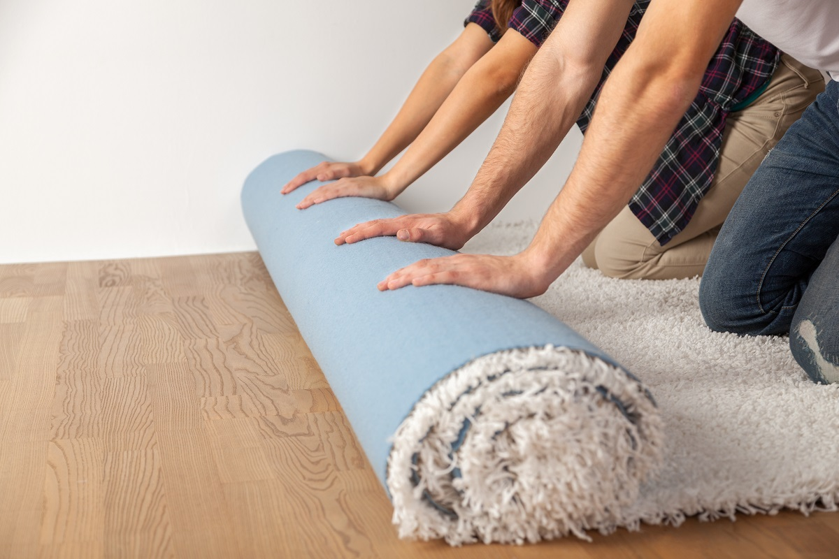 arms of three people rolling up a white shag area rug