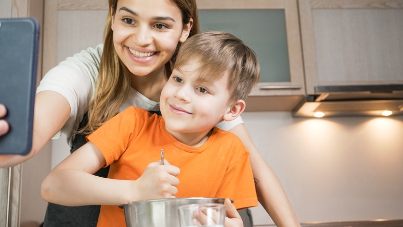 young mother with school age son smiling at handheld device while cooking