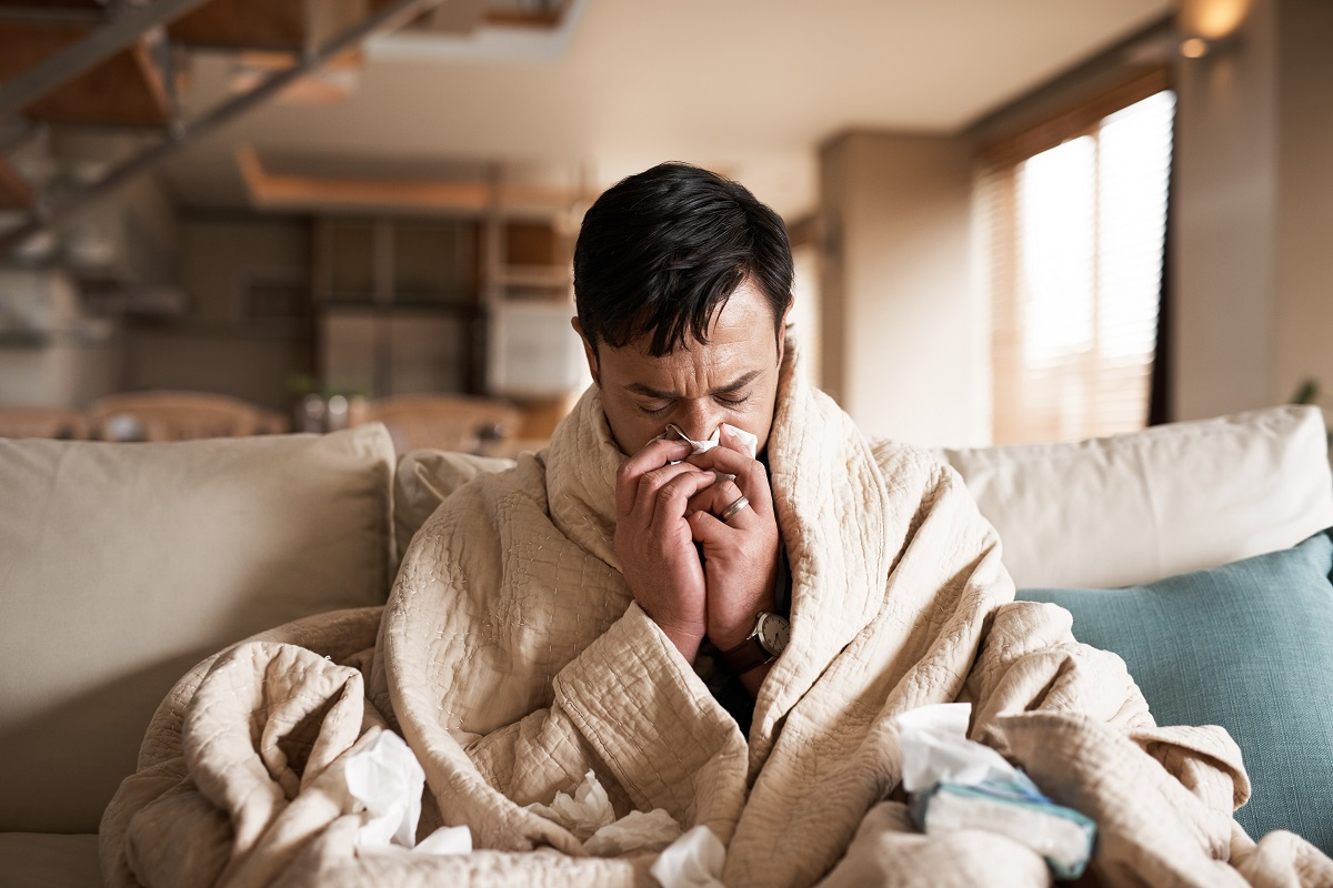 sick man staying home from work, wrapped in a blanket and blowing his nose