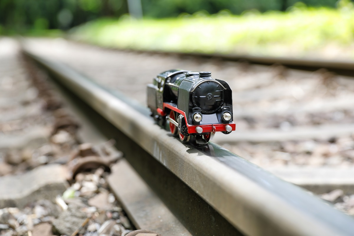 toy train engine perched on real railroad track