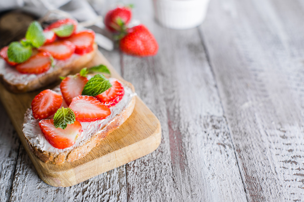View of two slices of toast topped with ricotta and strawberry slices, on a weathered gray table.