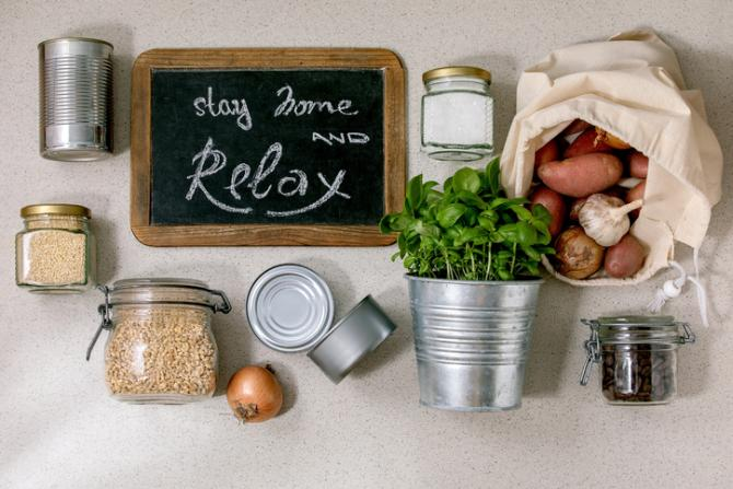 "Jarred grains, canned food, a bag of potatoes and a potted parsley plant surround a chalkboard that reads: ""Stay Home and Relax.""."""