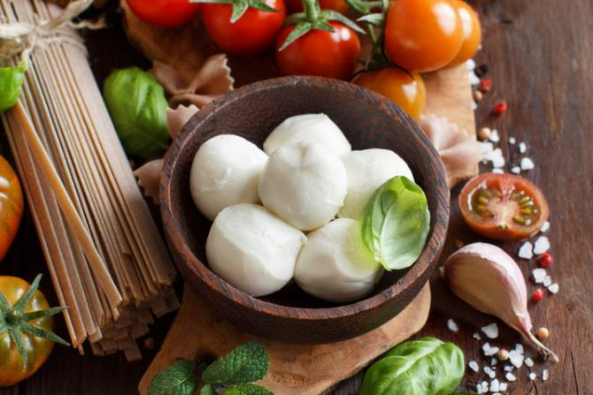Caprese ingredients, including fresh mozzarella, tomatoes, herbs, garlic cloves and whole-wheat linguine, arranged on a wooden cutting board.