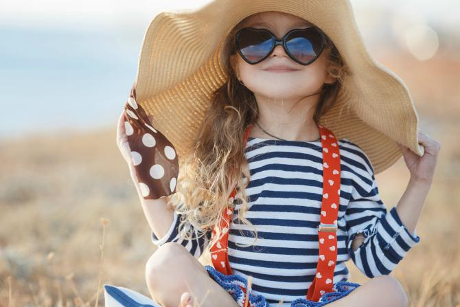Young girl wearing sunglasses and large sun hat in field_Is your child wearing the right type of sunscreen