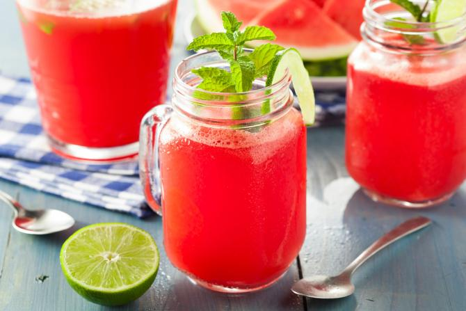 Glass mason jars filled with pink aguas frescas, served with fresh mint and lime.