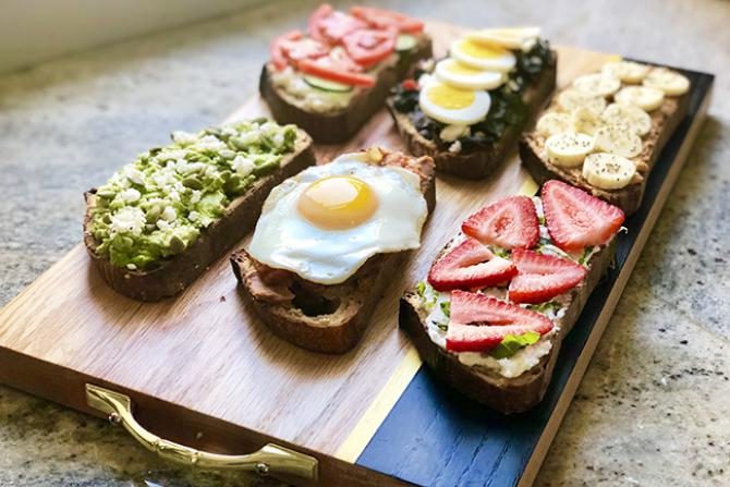 six open-faced breakfast toasts on wooden board