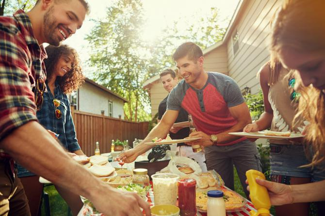 friends laughing and eating at a backyard cookout