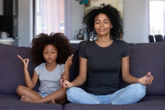 Mother and young daughter sit on a couch practicing mindful breathing together.