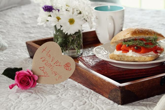 "Closeup view of a tray on a bed, set with a plate of smoked salmon bagel, a tea mug and a vase of white flowers. Heart-shaped card with child's handwriting reads ""Happy Mother's Day."""