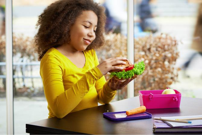 young african american girl getting ready to eat a healthy lunch at school