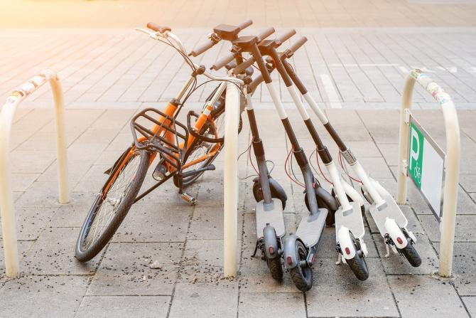 photo of bike rack with one bike and several electric scooters