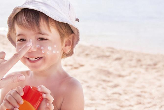 Child on beach in white hat getting sunscreen on his nose.