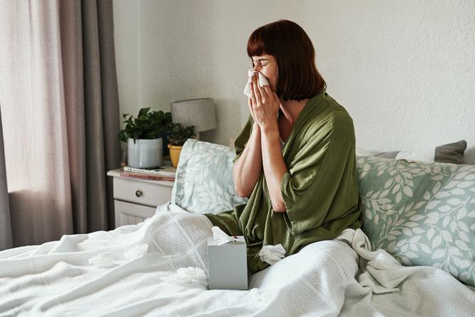 woman with allergies blowing her nose into a tissue while sitting in bed