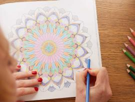 A woman enjoys coloring.